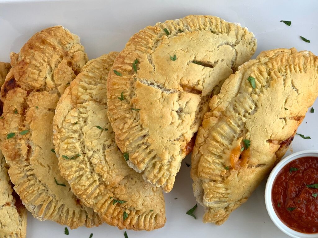 A plate of warm, handheld homemade calzones with a small bowl of pizza sauce for dipping