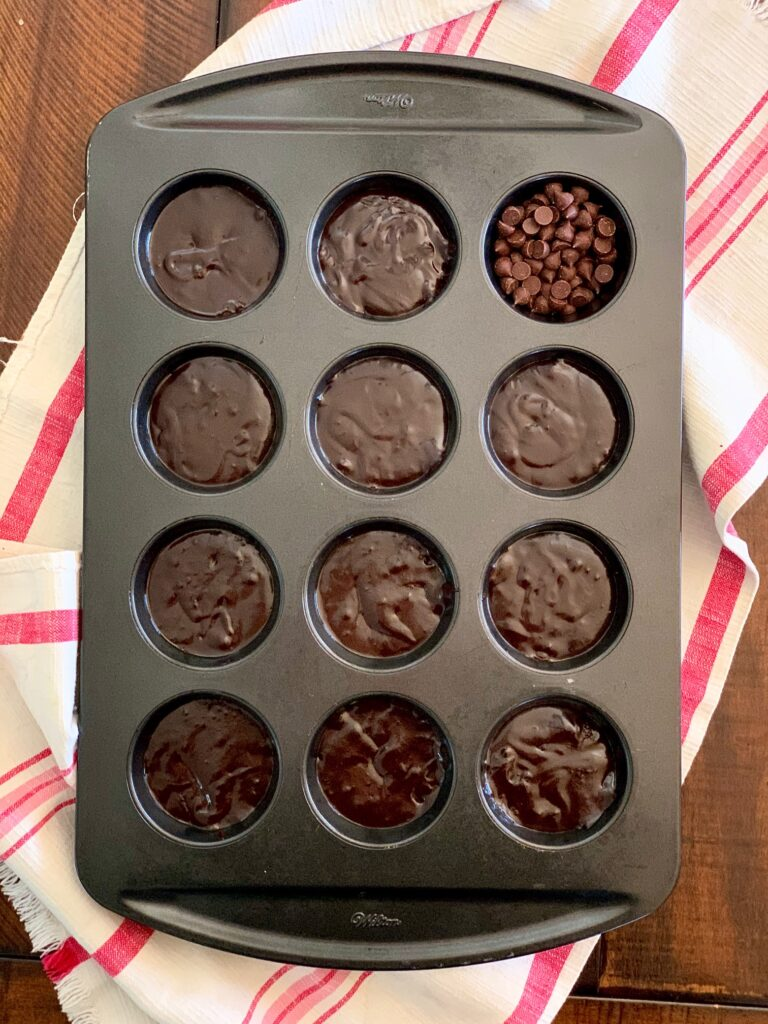 A muffin pan filled with brownie batter.