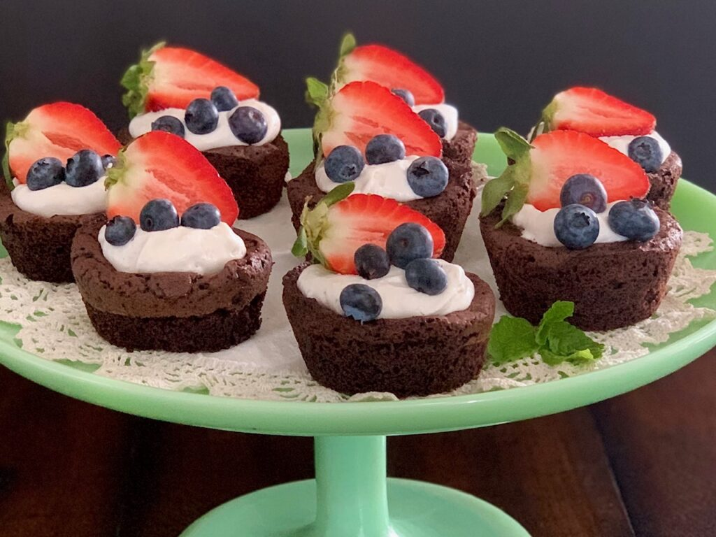 A plate of homemade brownie bites with whipped topping and fruit.