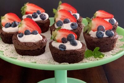 A serving plate full of homemade brownie bites topped with dairy free whipped topping and fruit.