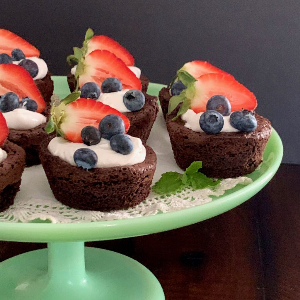 Homemade brownie bites on a serving tray topped with dairy free whipped topping and fruit.