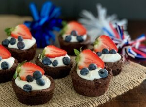 A dinning table full of mini brownie pieces then topped with cocowhip and blueberries and fruit.