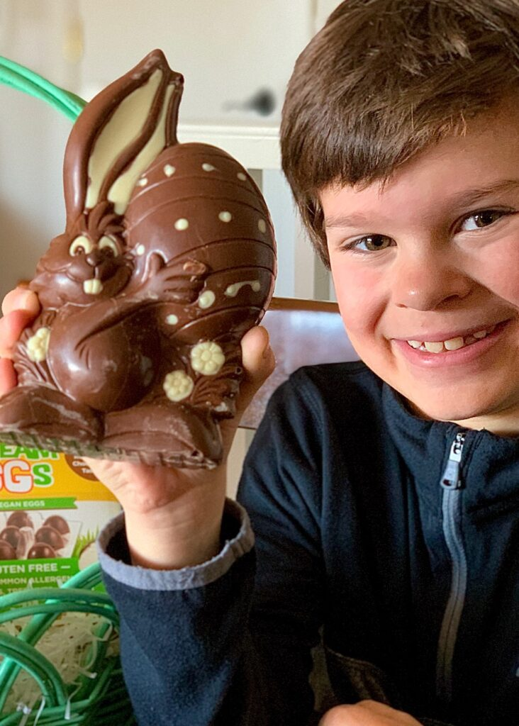 A boy holding a large chocolate bunny.