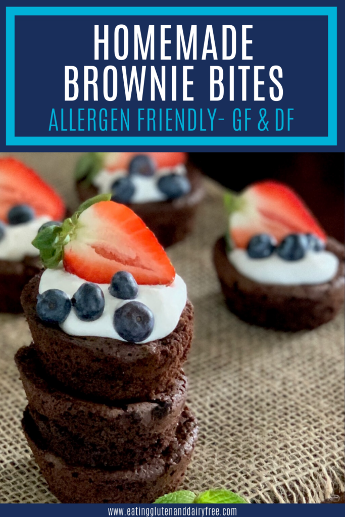 A stack of homemade brownie bites topped with dairy free whipped topping and fruit.