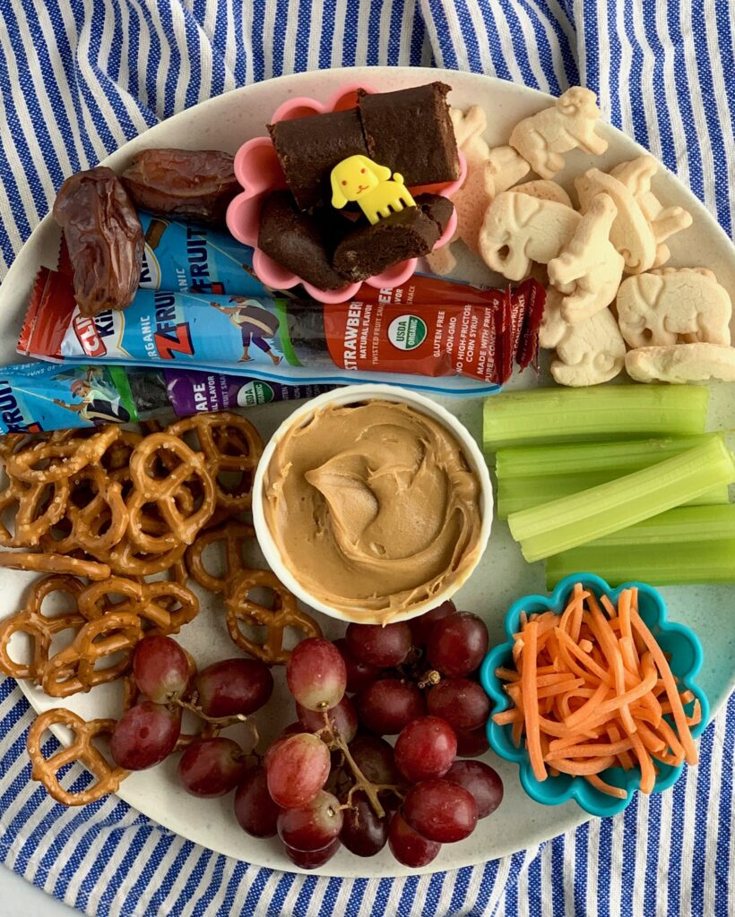 Several kid friendly snack ideas on a plate with peanut butter