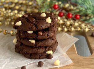 A stack of 3 chocolate cookies with white chocolate chips