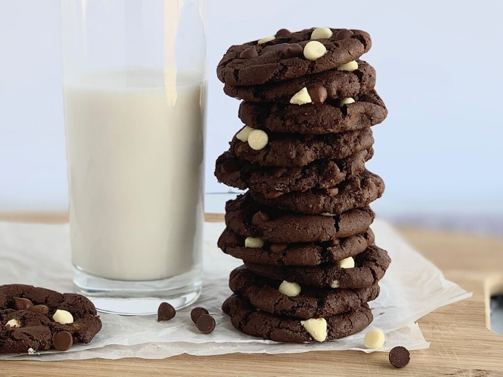 Several white chocolate chip cookies stacked next to a glass of almond milk.