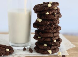 A large stack of white chocolate chip cookies next to a glass of milk