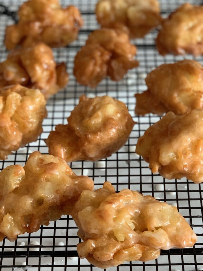 Deep fried apple fritters on a cooling wrack