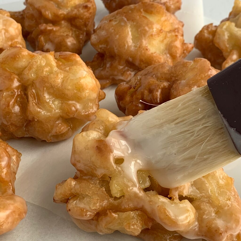 Brushing a glaze over deep fried apple fritters
