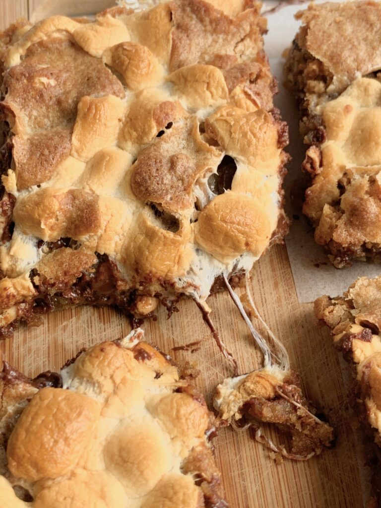 S'more cookie bars with gooey melted marshmallows oozing out.