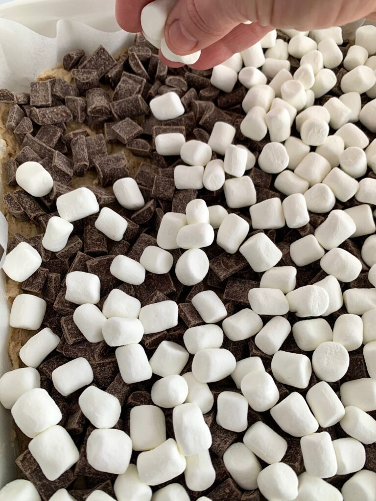 Spreading marshmallows on top of the chocolate chunks.