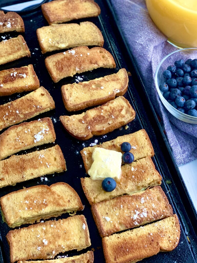 French Toast Sticks on a griddle with butter