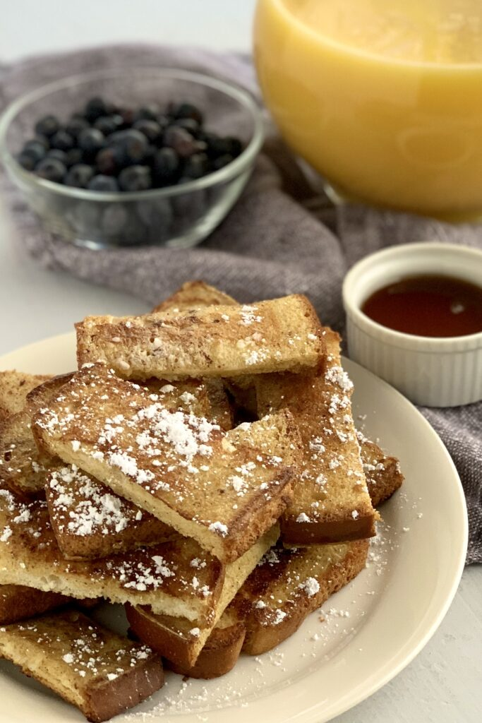 A plate heaping with french toast sticks