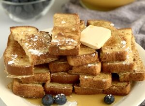 French toast sticks on a serving plate with dairy free butter and powered sugar.