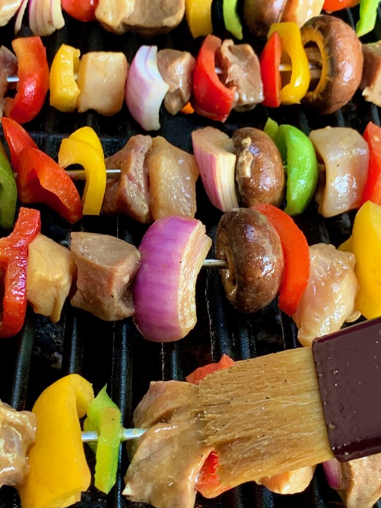 Shish Kabobs on the grill with a basting brush applying more marinade