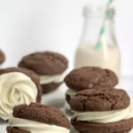 Buttercream frosting sandwiched between 2 brownie cookies.
