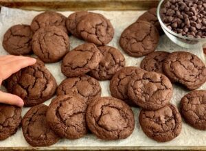 A child's hand reaching for a baking sheet full of fudgy brownie cookies.