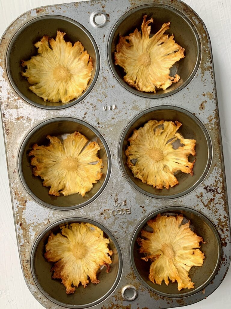 Pineapple slices drying in a muffin tin.