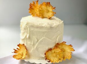 A 3 layer cake frosted with buttercream icing and garnished with dried pineapple flowers.