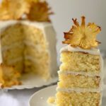 A slice of 3 layer pineapple cake frosted in buttercream frosting with a delicate dried pineapple flower on top
