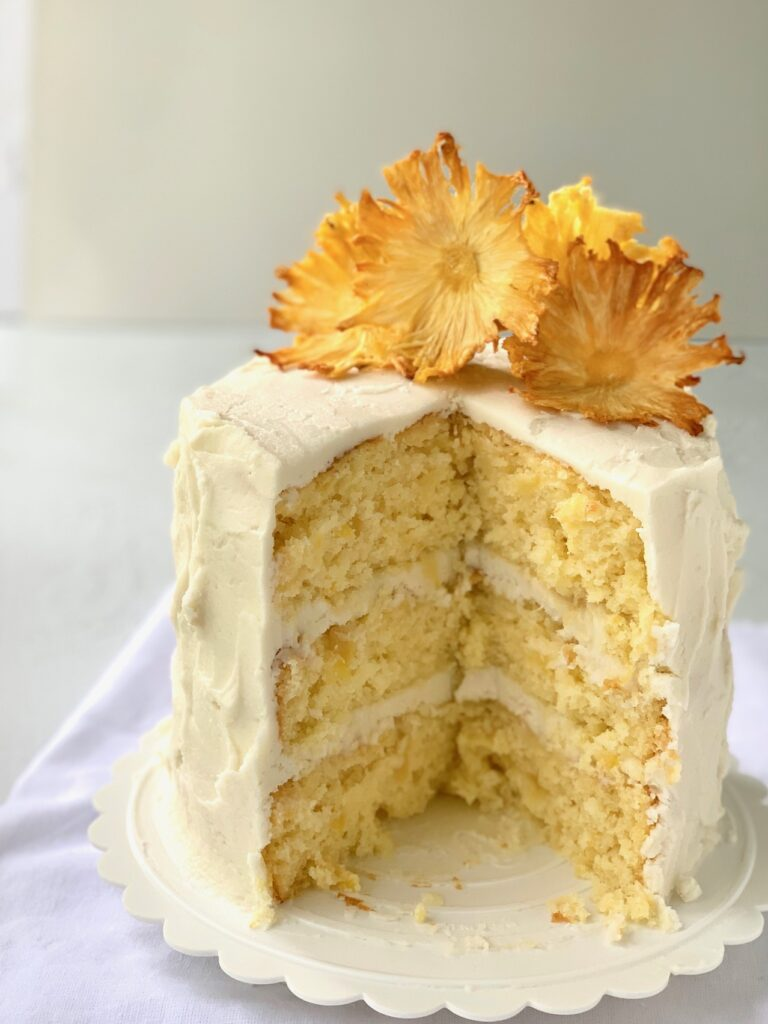 A 3 layer pineapple cake with buttercream frosting and dried pineapple slices that look like flowers
