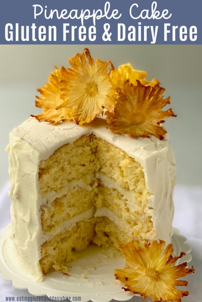 A 3 layer pineapple cake with buttercream frosting and dried pineapple slices that look like flowers.
