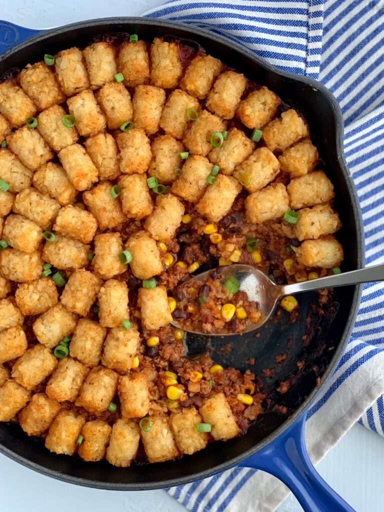 Tater tots over a taco mixture of ground beef, corn, black beans, and sauce mixtures.