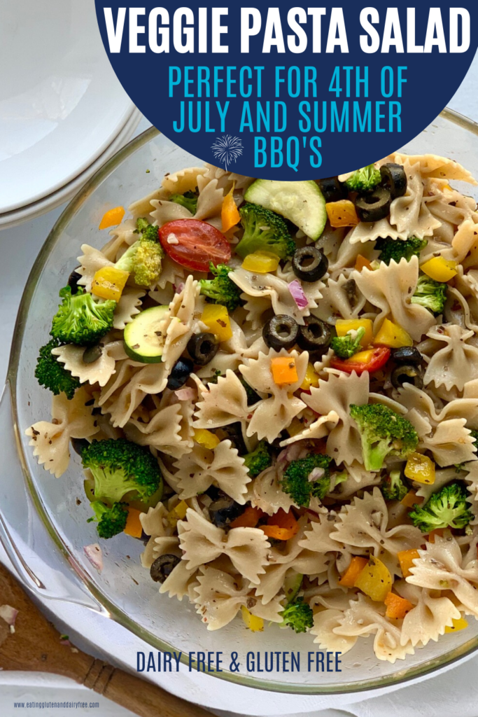 A veggie pasta salad with broccoli, tomatoes, olives, zucchini, and bell peppers.