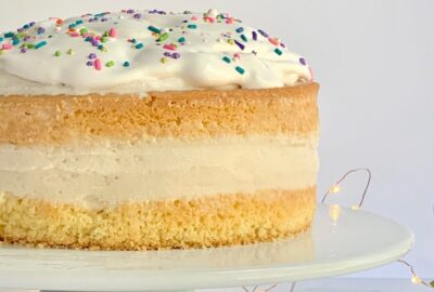 Ice cream sandwiched between a top and bottom layer of yellow cake mix then topped with whipped topping and sprinkles.