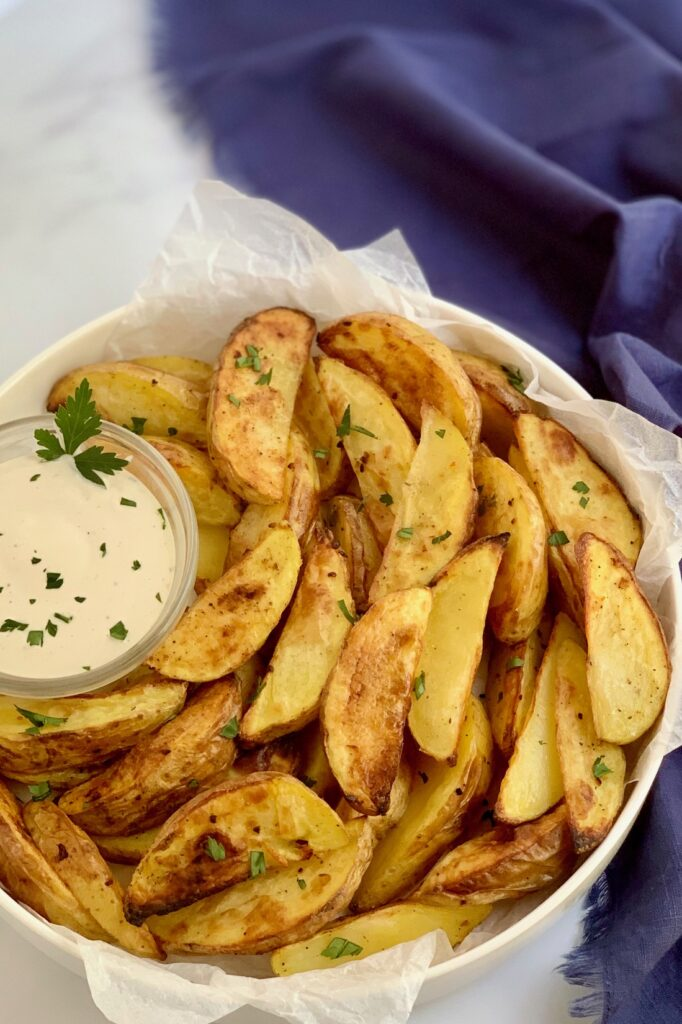 A plate heaping with baked potato wedges and dressing.