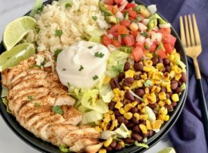 A bowl filled with iceberg lettuce, chicken, corn, black beans, cilantro lime rice, pico de gallo, and a dollop of sour cream.