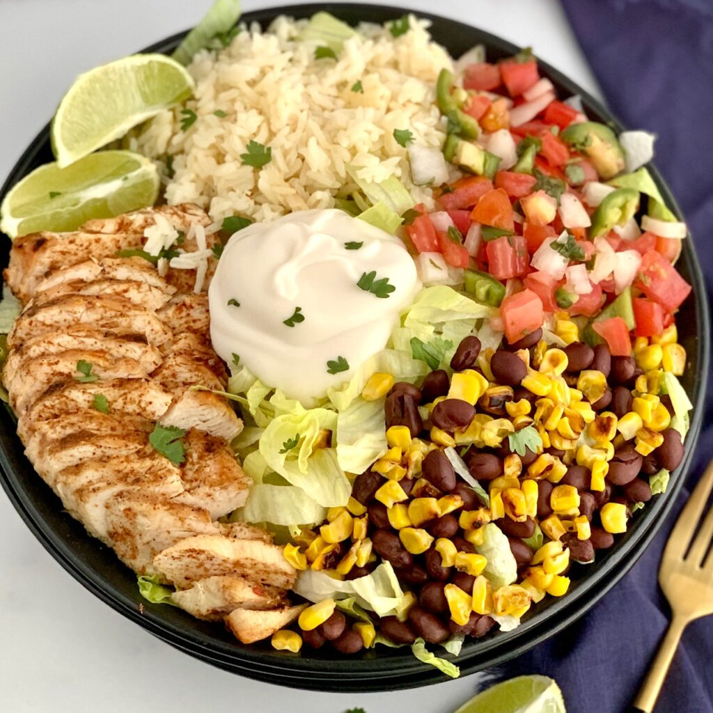 A bowl filled with iceberg lettuce, chicken, corn, black beans, cilantro lime rice, pico de gallo, and a dollop of sour cream.