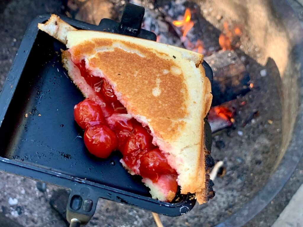 Cherry pie filling sandwiched between to slices of bread in a pie maker by the campfire.