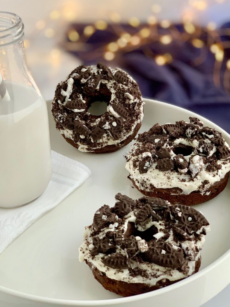 3 oreo donuts with frosting and crushed oreo cookies on top next to a glass of milk.