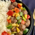 a bowl of white rice with meatballs, pineapple, and bell peppers