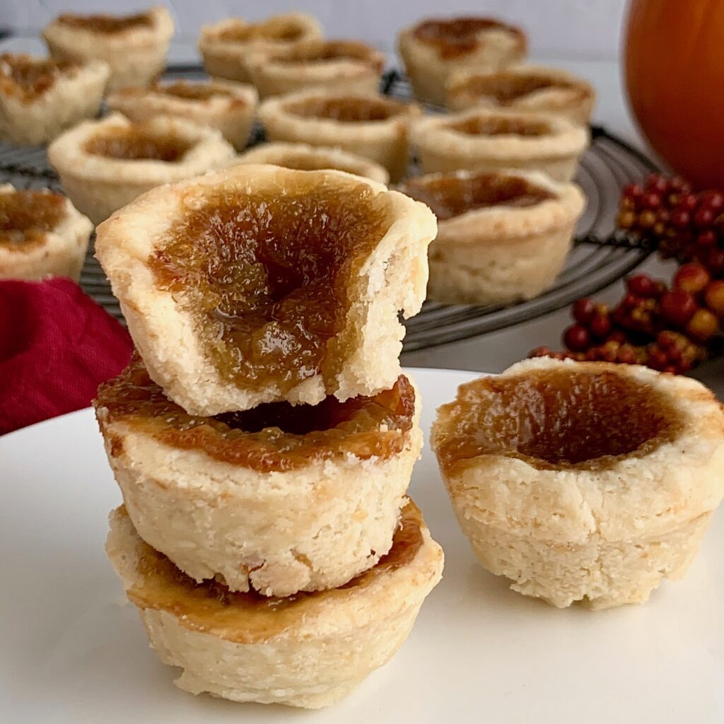 A stack of butter tarts with an ooey and gooey middle.