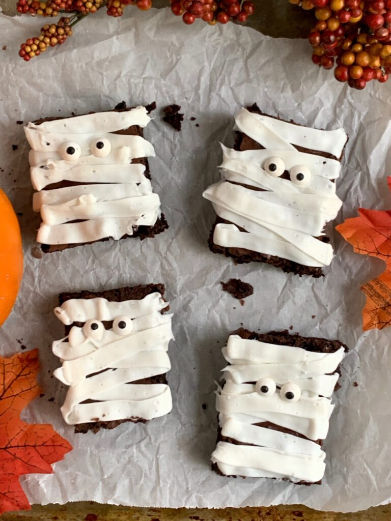 4 rectangle brownies with white frosting zig zagging back and forth and googly eyes making them look like mummies