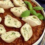 A bowl of pasta sauce and ricotta stuffed shells.