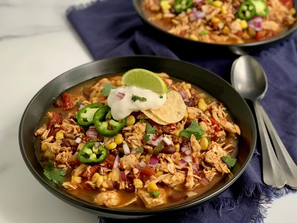 Two bowls loaded with taco soup including shredded chicken, beans, corn, tomatoes, onions, topped with a dollop of dairy free sour cream,green onions, and cilantro.