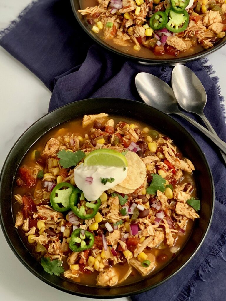 Two bowls crock-pot taco soup loaded with shredded chicken, beans, corn, tomatoes, onions, topped with a dollop of dairy free sour cream,green onions, and cilantro.