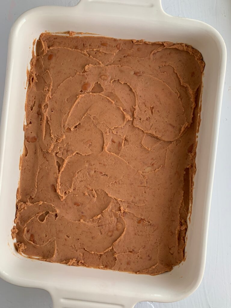 A baking dish will with a layer of refried beans.
