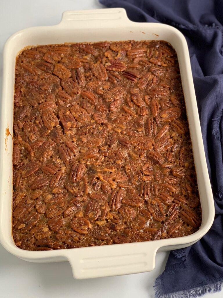 A baked sheet pan of pecan pie bars.