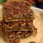 3 pecan pie bars stacked on top of each other.
