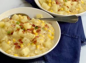 A bowl full of creamy potato corn chowder topped with bacon and green onions.
