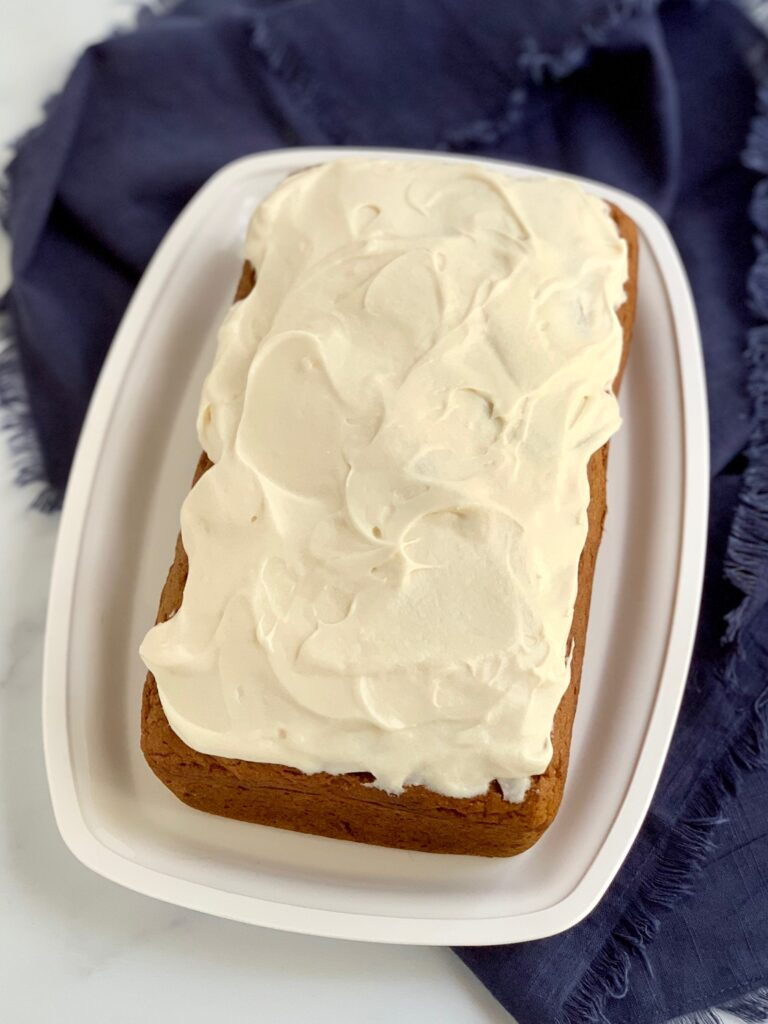 A loaf of pumpkin bread with cream cheese frosting.