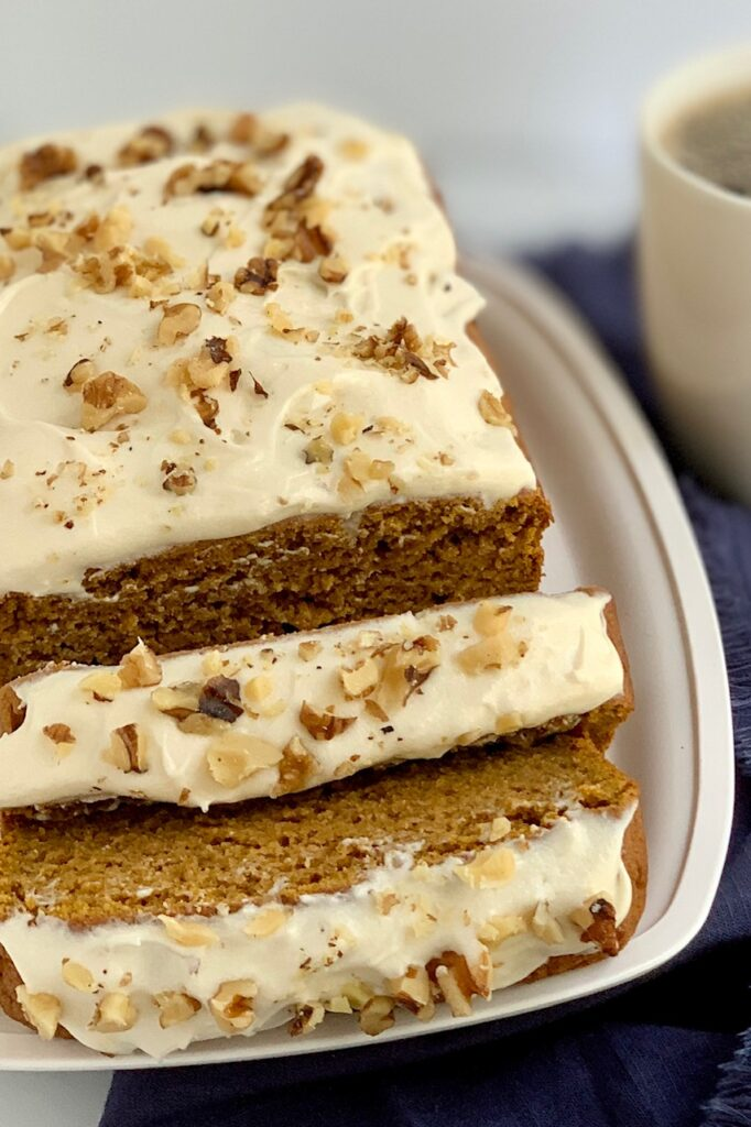 Slices of pumpkin bread with cream cheese frosting and chopped walnuts,