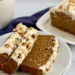 Slices of pumpkin bread with cream cheese frosting on top with crushed walnuts.