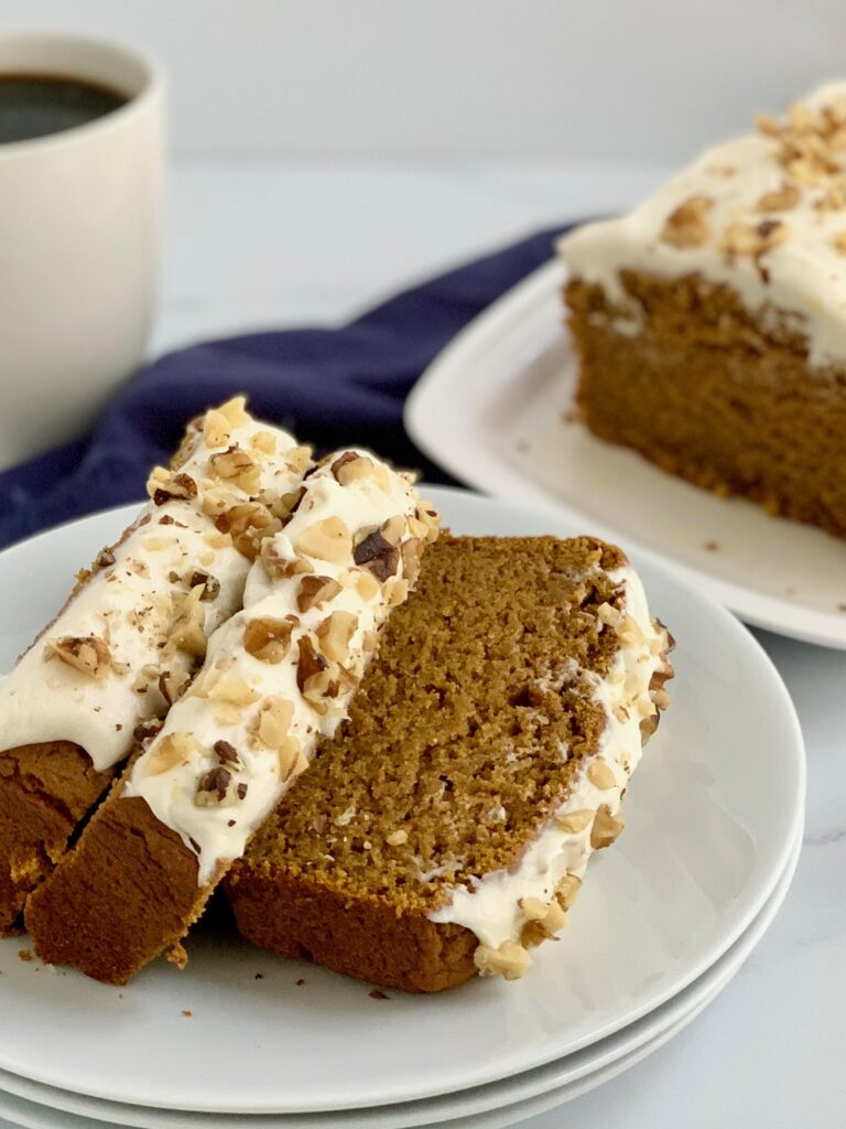 3 slices of pumpkin bread with cream cheese frosting and walnuts on a plate
