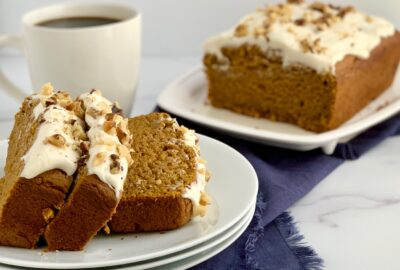 Slices of pumpkin bread with cream cheese frosting and chopped walnuts.